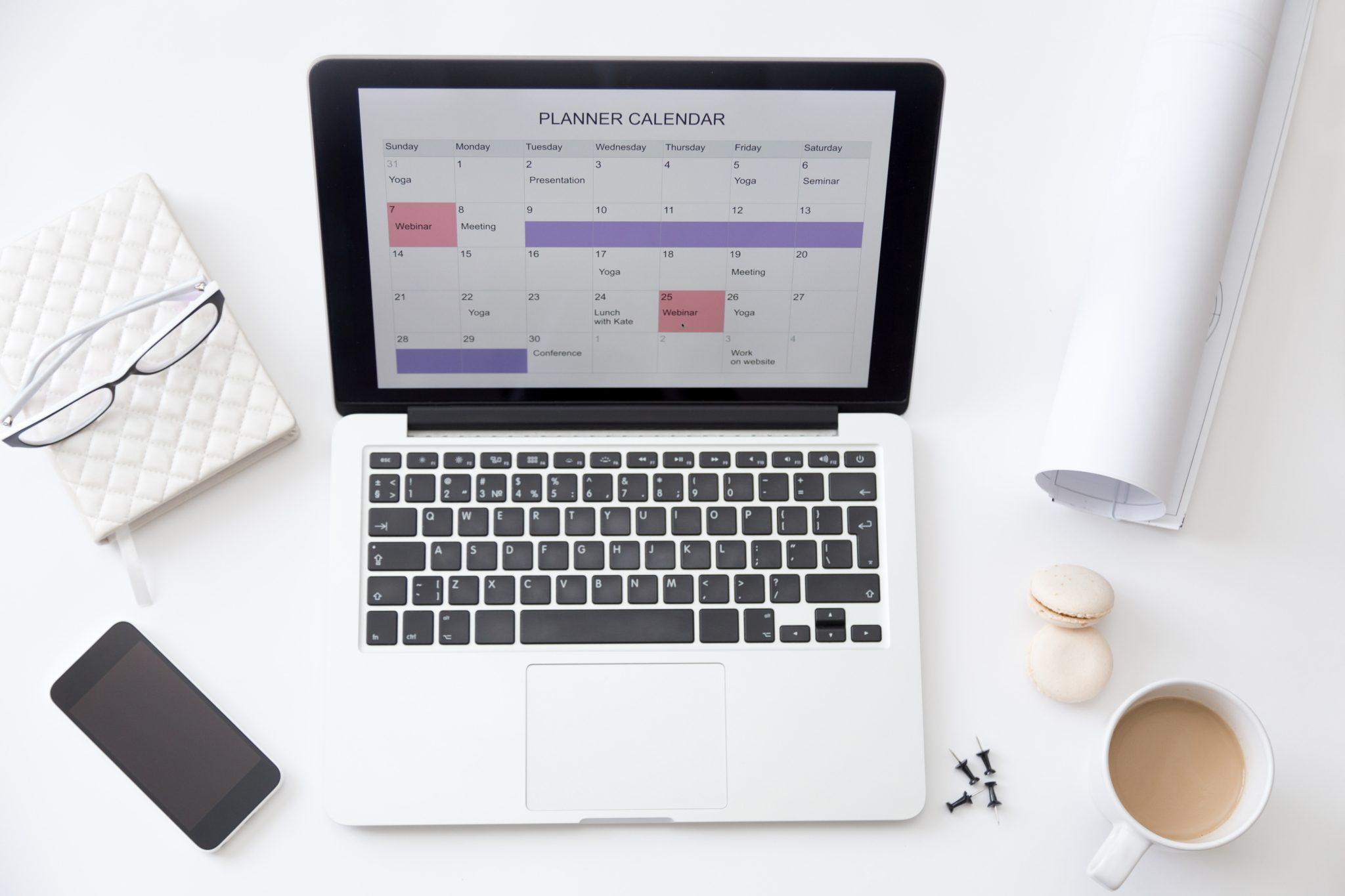 Escritorio de trabajo con ordenador portátil que muestra una aplicación de calendario en su pantalla.
